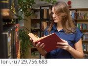 Купить «Девушка читает книгу у стеллажа в библиотеке», фото № 29756683, снято 15 января 2019 г. (c) Иванов Алексей / Фотобанк Лори