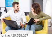 Купить «Friendly young woman and man relaxing in cozy hostel lobby, spending time with laptop and book», фото № 29768267, снято 24 мая 2018 г. (c) Яков Филимонов / Фотобанк Лори