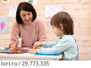 Купить «Llittle girl is working with color paper», фото № 29773335, снято 22 мая 2019 г. (c) Оксана Кузьмина / Фотобанк Лори