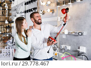 Купить «Happy couple customers trying use modern desk lamp», фото № 29778467, снято 29 января 2018 г. (c) Яков Филимонов / Фотобанк Лори