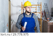 Купить «plasterer is looking on the project of work for the object.», фото № 29778975, снято 3 июня 2017 г. (c) Яков Филимонов / Фотобанк Лори