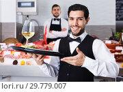 Купить «Waiter holding tray with seafood dishes at fish restaurant again», фото № 29779007, снято 26 января 2018 г. (c) Яков Филимонов / Фотобанк Лори