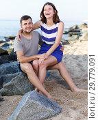 Купить «Happy loving couple sitting and hugging», фото № 29779091, снято 27 июня 2018 г. (c) Яков Филимонов / Фотобанк Лори