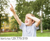 Купить «Boy 5 years old looks up at something and shows finger in summer park on background of trees», фото № 29779519, снято 28 августа 2018 г. (c) Юлия Бабкина / Фотобанк Лори
