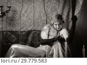 Купить «Girl in an evening dress with a cigarette mouthpiece. Studio portrait in retro style, toned in sepia», фото № 29779583, снято 27 декабря 2018 г. (c) Вадим Орлов / Фотобанк Лори