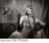 Купить «Girl in an evening dress with a cigarette mouthpiece. Studio portrait in retro style, toned in sepia», фото № 29779591, снято 27 декабря 2018 г. (c) Вадим Орлов / Фотобанк Лори