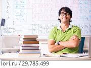 Купить «Young male student chemist in front of periodic table», фото № 29785499, снято 19 октября 2018 г. (c) Elnur / Фотобанк Лори
