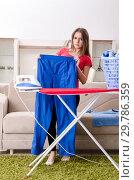 Купить «Young beautiful woman ironing at home», фото № 29786359, снято 30 октября 2018 г. (c) Elnur / Фотобанк Лори