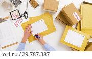 Купить «woman signing parcel envelopes at post office», видеоролик № 29787387, снято 19 января 2019 г. (c) Syda Productions / Фотобанк Лори