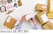 Купить «woman signing parcel boxes at post office», видеоролик № 29787391, снято 19 января 2019 г. (c) Syda Productions / Фотобанк Лори