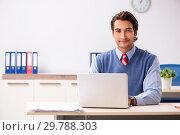 Купить «Young handsome employee working in the office», фото № 29788303, снято 5 октября 2018 г. (c) Elnur / Фотобанк Лори