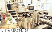 Купить «View of empty restaurant kitchen with professional equipment and products», видеоролик № 29794439, снято 16 октября 2018 г. (c) Яков Филимонов / Фотобанк Лори