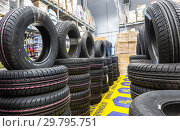 Купить «Brand new tires stacked up for sale in the chain hypermarket», фото № 29795751, снято 24 марта 2018 г. (c) FotograFF / Фотобанк Лори