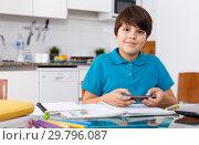 Купить «Boy using phone while doing homework», фото № 29796087, снято 17 ноября 2018 г. (c) Яков Филимонов / Фотобанк Лори