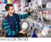 Купить «Young male choosing fishing variety accessories in the sports shop», фото № 29796183, снято 16 января 2018 г. (c) Яков Филимонов / Фотобанк Лори