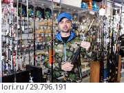 Купить «Male customer in fishing clothing choosing fishing rod», фото № 29796191, снято 16 января 2018 г. (c) Яков Филимонов / Фотобанк Лори