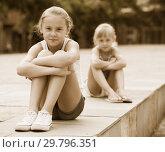 Купить «Small sisters upset after quarrel outside», фото № 29796351, снято 20 июля 2017 г. (c) Яков Филимонов / Фотобанк Лори