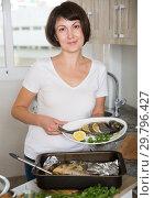 Купить «Housewife demonstrating dorado fish», фото № 29796427, снято 22 ноября 2018 г. (c) Яков Филимонов / Фотобанк Лори