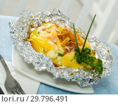 Cooked baked potatoes in foil with filling of bacon, fried onion and cheese. Стоковое фото, фотограф Яков Филимонов / Фотобанк Лори