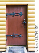 Купить «Traditional russian wooden door with forged massive metal hinges in the house from logs», фото № 29797151, снято 18 августа 2017 г. (c) FotograFF / Фотобанк Лори