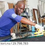 Купить «attentive African American glazier choosing glass for cutting in workshop», фото № 29798783, снято 16 мая 2018 г. (c) Яков Филимонов / Фотобанк Лори
