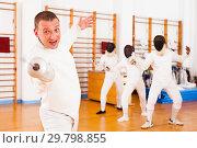 Купить «Sporty young man fencer practicing effective fencing techniques», фото № 29798855, снято 11 июля 2018 г. (c) Яков Филимонов / Фотобанк Лори