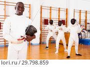 Купить «African american male fencer in uniform standing with mask and foil», фото № 29798859, снято 11 июля 2018 г. (c) Яков Филимонов / Фотобанк Лори