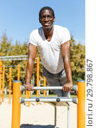 Купить «Athletic african american male performs warm-up exercises at chin-up bar», фото № 29798867, снято 3 ноября 2018 г. (c) Яков Филимонов / Фотобанк Лори