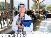 Купить «Mature female milker with clipboard standing at cowshed», фото № 29813331, снято 24 октября 2017 г. (c) Яков Филимонов / Фотобанк Лори