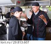 Купить «Angry chef talking to female assistant», фото № 29813607, снято 24 сентября 2018 г. (c) Яков Филимонов / Фотобанк Лори