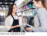 Купить «Young woman hairdresser helping woman client with choice of shampoo in shop», фото № 29813727, снято 31 марта 2018 г. (c) Яков Филимонов / Фотобанк Лори