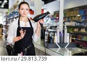 Купить «Young female hairdresser holding blow dryer and hair cutters in shop», фото № 29813739, снято 31 марта 2018 г. (c) Яков Филимонов / Фотобанк Лори