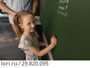 Купить «High angle view of schoolgirl writing on chalk board in classroom», фото № 29820095, снято 10 ноября 2018 г. (c) Wavebreak Media / Фотобанк Лори