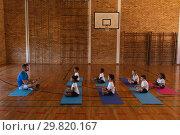 Купить «Yoga teacher teaching yoga to school kids in school», фото № 29820167, снято 10 ноября 2018 г. (c) Wavebreak Media / Фотобанк Лори