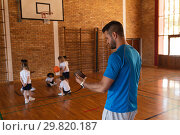 Купить «Basketball coach using digital tablet at basketball court in school», фото № 29820187, снято 10 ноября 2018 г. (c) Wavebreak Media / Фотобанк Лори