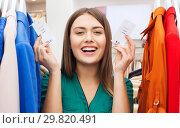 Купить «happy woman with price tags at clothing store», фото № 29820491, снято 19 февраля 2016 г. (c) Syda Productions / Фотобанк Лори
