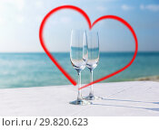 two champagne glasses framed by red heart shape. Стоковое фото, фотограф Syda Productions / Фотобанк Лори