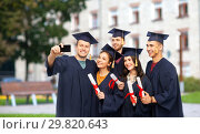 Купить «graduates with diplomas taking selfie by cellphone», фото № 29820643, снято 10 ноября 2018 г. (c) Syda Productions / Фотобанк Лори
