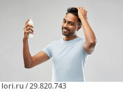 Купить «smiling indian man applying hair spray over gray», фото № 29820743, снято 27 октября 2018 г. (c) Syda Productions / Фотобанк Лори