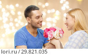 Купить «man giving woman flowers over festive lights», фото № 29821035, снято 9 февраля 2014 г. (c) Syda Productions / Фотобанк Лори