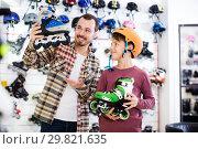 Купить «Seller assisting boy in choosing roller-skates», фото № 29821635, снято 21 декабря 2016 г. (c) Яков Филимонов / Фотобанк Лори