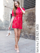 Купить «portrait of young female in sexually red gown with pumps in hands standing in town», фото № 29821663, снято 24 июня 2017 г. (c) Яков Филимонов / Фотобанк Лори