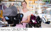 Positive pregnant woman looking for baby seat. Стоковое фото, фотограф Яков Филимонов / Фотобанк Лори