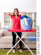 Купить «Young beautiful woman ironing at home», фото № 29824991, снято 30 октября 2018 г. (c) Elnur / Фотобанк Лори