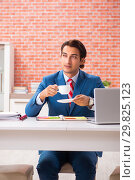 Купить «Young handsome employee working in the office», фото № 29825123, снято 11 сентября 2018 г. (c) Elnur / Фотобанк Лори