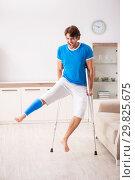 Купить «Leg injured young man with crutches at home», фото № 29825675, снято 19 сентября 2018 г. (c) Elnur / Фотобанк Лори