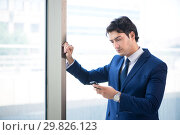 Купить «Young handsome businessman standing at the window», фото № 29826123, снято 2 августа 2018 г. (c) Elnur / Фотобанк Лори