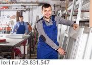 Купить «Young laborer is inspecting the window frame», фото № 29831547, снято 30 марта 2017 г. (c) Яков Филимонов / Фотобанк Лори