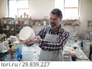 Купить «Focused male potter examining his creation for flaws», фото № 29839227, снято 6 августа 2017 г. (c) Wavebreak Media / Фотобанк Лори