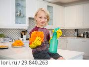 Купить «Boy holding rag and spray bottle in kitchen», фото № 29840263, снято 3 августа 2017 г. (c) Wavebreak Media / Фотобанк Лори